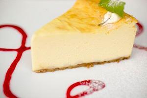 Tvarohový koláč na talíři zdobené malinovým sirupem