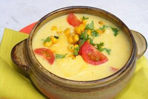 Жълта царевица, зеленина и домати в глинен съд