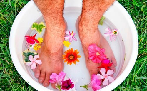 Pánské nohy v povodí s vodou a květinami