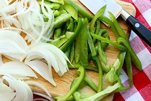 Нарязан лук и зелен пипер на дъска за рязане