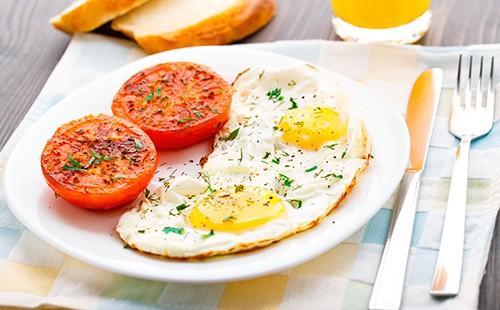 Smažená vejce s rajčaty na talíři