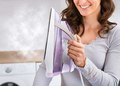 Smějící se žena držící žehličku