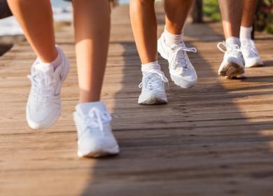 Бели маратонки на краката на тичащи хора
