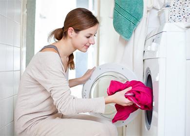 Žena dá červený svetr do pračky