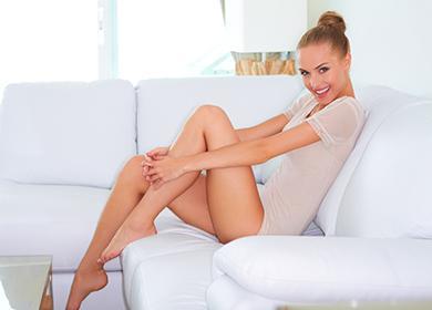 Красива жена кокетливо седи на бял диван