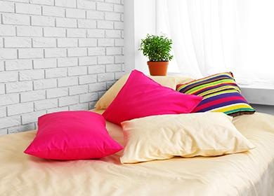 Vícebarevné polštáře na posteli