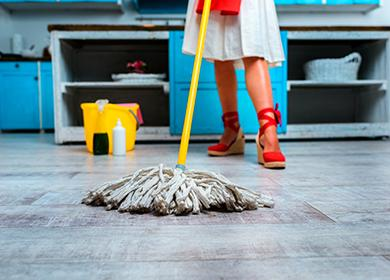 Ženské nohy v červené boty, žluté kbelík a mop