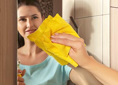 Žena tře zrcadlo se žlutým ubrouskem