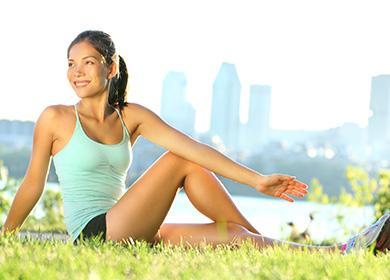 Момиче в природата прави упражнения.