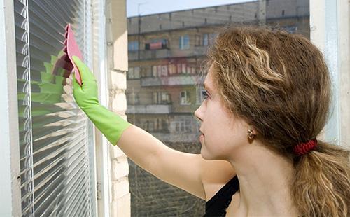 Žena myje žaluzie