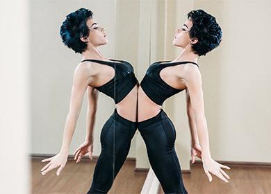 Жената се занимава със спорт близо до огледалото