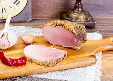 Kousek vařeného vepřového masa, hlava česneku a lusek pepře