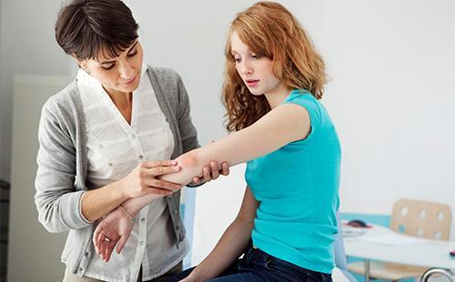 Лекарят изследва лакътя на пациента