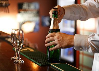 Bartender otevírá láhev šampaňského