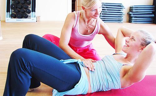 Жена се занимава със спорт с инструктор