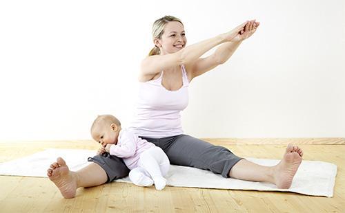 Жена прави упражнения у дома с бебе