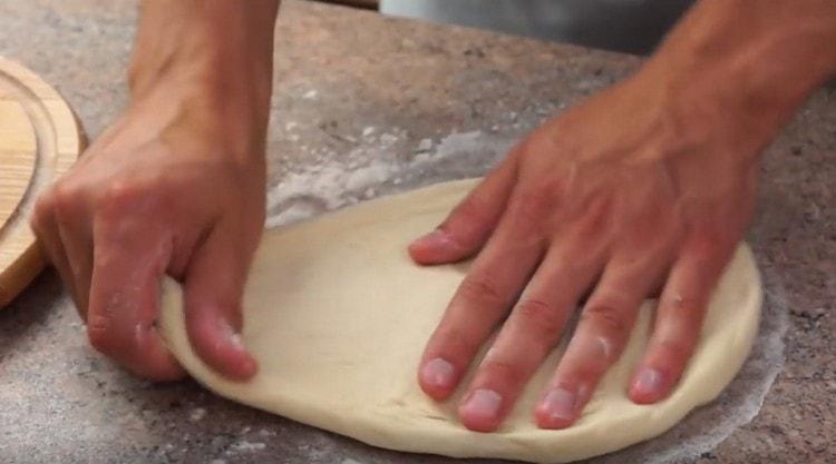 Разтегнете тестото с ръце или разточете.