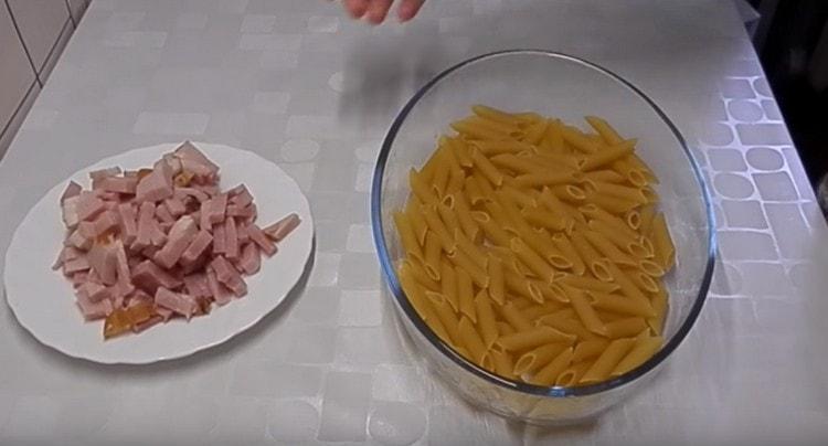 На дъното на формата разпределете макароните на един слой.