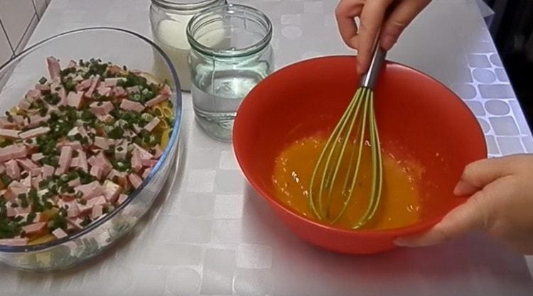 Разбийте яйцата с подправките.