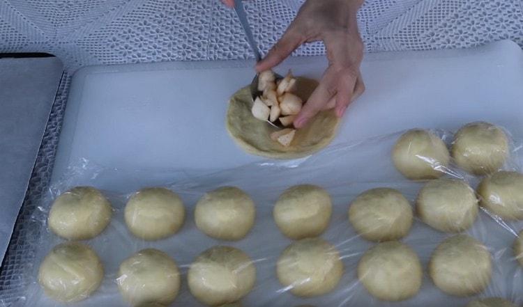 Vaivaa jokainen taikinapallo kädellä kakkuun ja laita omenatäyte sen keskelle.