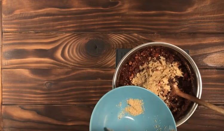 V čokoládové hmotě rozetřeme směs sušenek a ořechů, promícháme.