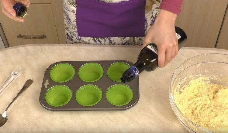 Formy na pečení muffinů namazané rostlinným olejem.